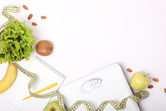 floor scales, tape measure and healthy products on a colored background top view. The concept of a healthy diet, body weight control. Healthy lifestyle.
