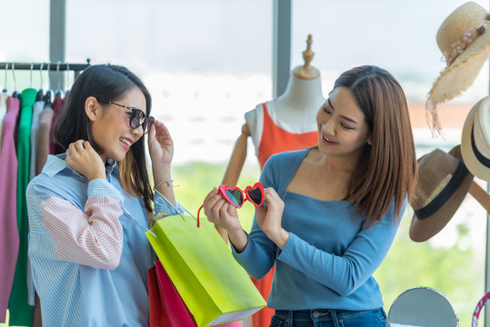 Young travel shopping woman choosing sunglasses with friend at clothes shopping mall centre.