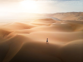 Woman walking on the desert sand dunes aerial view Wall mural