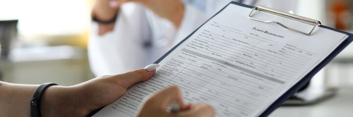 Female visitor filling out medicine documents in doctor office close-up