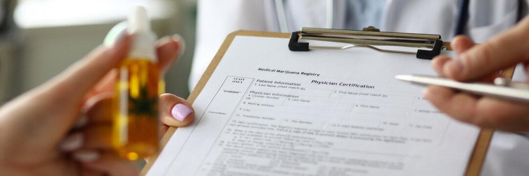 Female GP holding legal paper document clipped to pad for marijuana recipe closeup