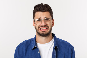 Close up portrait of disappointed stressed bearded young man in shirt over white background. Papier Peint