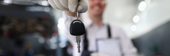 Focus on automechanic male hand holding automobile bunch of keys and important paper folder with information about fixed auto. Machinery checkup concept. Blurred background