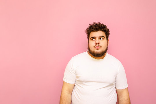 Funny fat man in white T-shirt and curly hair with serious face isolated on pink background, looks away at copy space. Funny overweight man wearing white t-shirt stands on colored background.