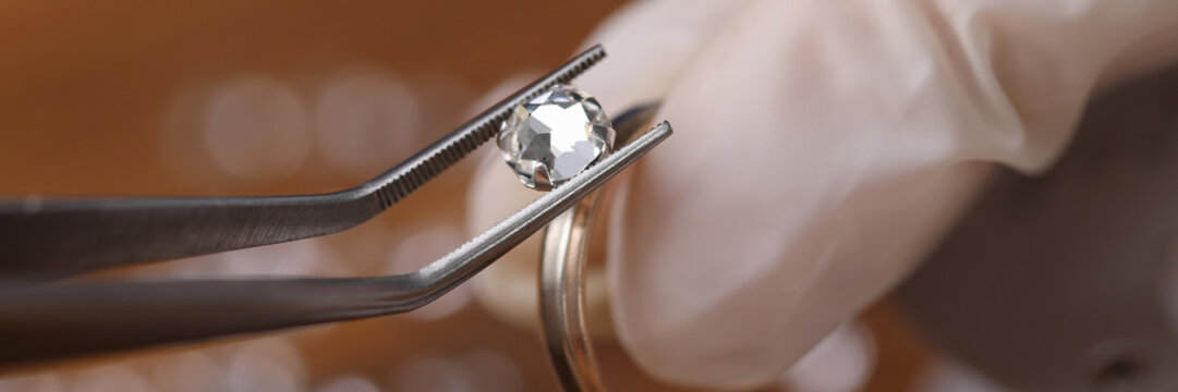 Jeweler install loose cut moissanite color round brilliant in ring DIY material diamond against wood table background. Make and repair jewelry to order concept