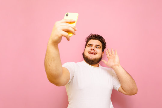 Funny fat man with a beard holds a smartphone in his hand and phone over a video call, isolated on a pink background.Overweight man communicates on video with a smile on his face. Copy space