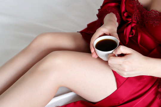 Cup of coffee in female hands, sexy woman in silk red nightie sitting on bed. Concept of relaxing at home, cozy morning, enjoying hot drink