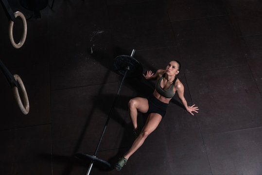 Young strong muscular fit girl with big muscles taking a break after hard strength weightlifing or dead lift crossfit workout training with barbell weights in the gym lying on the floor real people