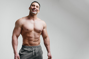 Sporty, sexy athlete smiling on a white background. Fitness