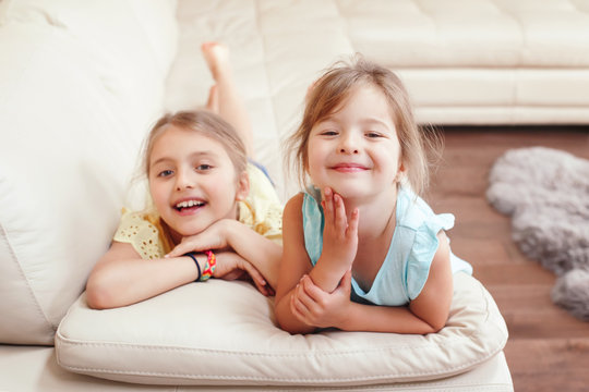 Two cute little Caucasian girls siblings playing at home. Adorable smiling children kids lying on a couch together. Authentic candid lifestyle domestic life moment. Happy friends sisters relationship.