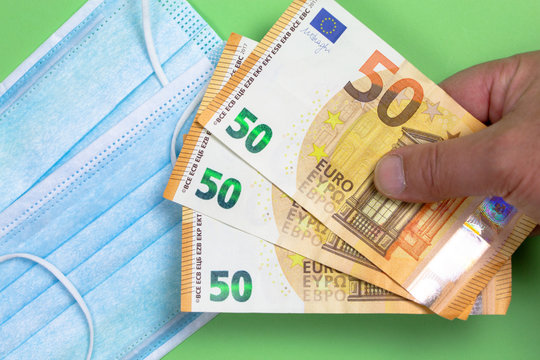 Protective surgical mask with several 50 euro notes held by a man's hand to illustrate the skyrocketing prices due to out of stock