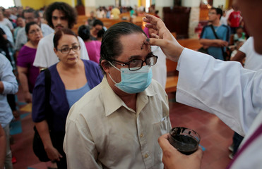 A Catholic man wearing a mask receives a cross of ashes on his forehead during a mass to celebrate Ash Wednesday in the Metropolitan Cathedral in Managua