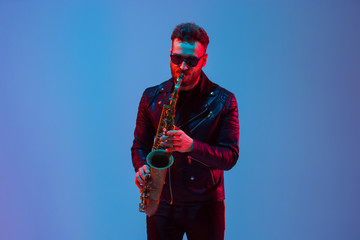 Young caucasian jazz musician playing the saxophone on gradient blue-purple studio background in neon light. Concept of music, hobby, festival. Joyful attractive guy. Colorful portrait of artist. Fotomurales