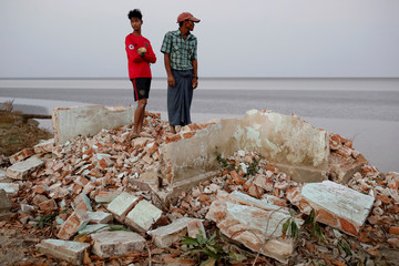 Myo Zaw and his father Aung So Oo stand at the ruins of a monastery after the riverbank it was located on collapsed into the water in Ta Dar U village, Bago, Myanmar