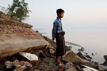 A student stands near the rubble of a school after it collapsed into the water in Ta Dar U village, Bago, Myanmar