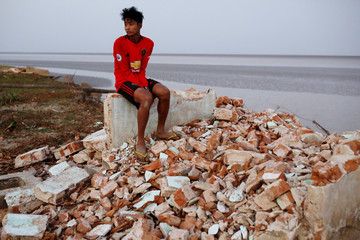 Myo Zaw sits at the ruins of a monastery after the riverbank it was located on collapsed into the water in Ta Dar U village, Bago, Myanmar