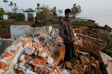 Myo Zaw stands amid the ruins of a monastery after the riverbank is was located on collapsed into the water in Ta Dar U village,Bago, Myanmar