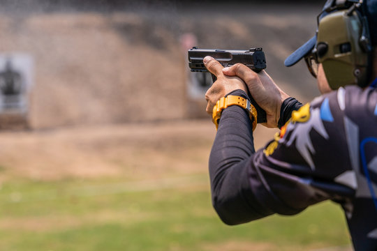 selective focus of man holding and fire handgun in gun shooting competition