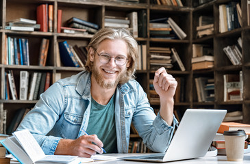 Portrait young bearded male college student glasses sit at home library desk handwrite notebook hold pen make notes from textbook laptop prepare project study online exam test web e education concept.