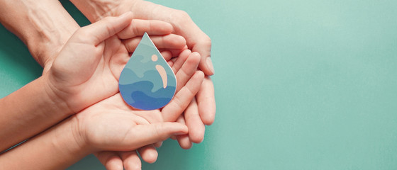 Adult and child hands holding water drop, World Water Day,  Clean water and sanitation, hand...