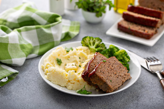 Meatloaf with spicy glaze sliced on a plate with mashed potatoes and broccoli, ground beef and pork dish
