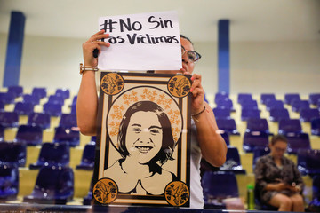 A woman holds a picture of her mother during a congress session to protest against approving an amnesty bill that exempts the prosecution of crimes committed during the civil war, in San Salvador, El Salvador