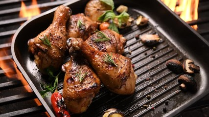 Wall Mural - Close up grill roast bbq chicken leg with addition herbs and spices on the frying pan on the flaming grill . 4k