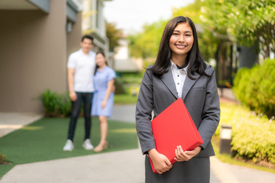 Asian confident woman real estate agent or realtor in suit holding red file and smile with young couple home sellers behind in front of house. Portrait of a lovely female broker..
