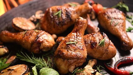 Wall Mural - Close up grill roast bbq chicken leg with addition herbs and spices on the frying pan on the flaming grill .