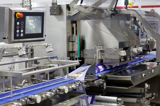 A fragment of the packaging system. Automatic conveyor for food packaging. Conveyor belt at a food factory.