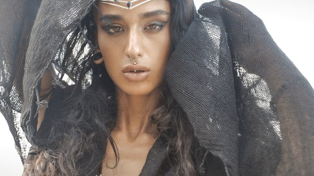 Oriental woman in dark clothes sensually posing