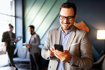 Handsome businessman checking emails on the phone in modern office Wall mural