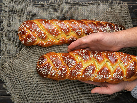 freshly baked sweet braided bread on a cloth, dark wooden background, top view. challah is laid out on the table, male hands