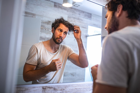 Handsome young man touching his hair with hand and grooming in bathroom at home. White metrosexual man worried for hair loss and looking at mirror his receding hairline.