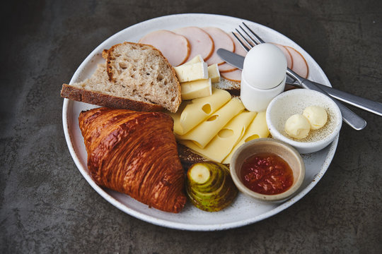 Continental breakfast with croissant, ham, cheese, egg, jam and fruit