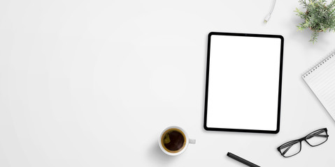 Office desk with tablet mockup and negative space. Cup of coffee, plant, glasses, pen and pad beside. Hero, header image or banner composition