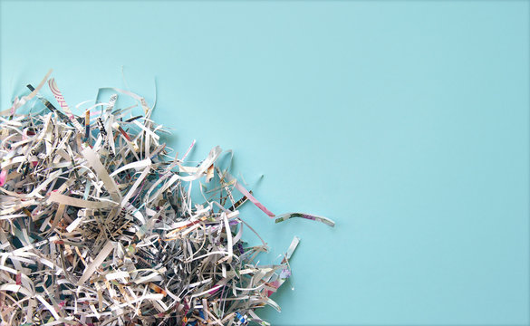 Shredded paper on light blue background. Selective focus image.