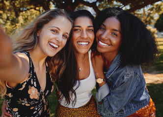 Close-up self portrait of smiling young multiethnic female friends taking selfie in the park - women taking a selfie in the park on a bright day