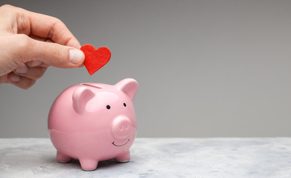 Donor. A man holds a red heart in his hand and goes to the piggy bank as a donation. Gray background