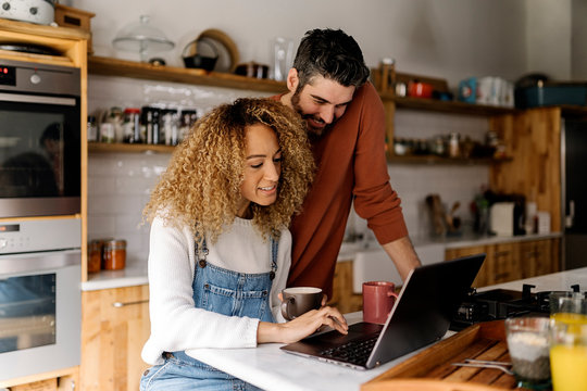 Couple looking at laptop in kitchen.