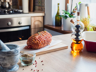Raw turkey meatloaf on table. Uncooked spicy pork meat roulade prepared to roast, marinated with spices and herbs on a wooden plate. Olive oil in glass bottle.