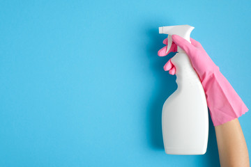 Female hand in pink glove holding cleaning spray bottle on blue background. House cleaning or housekeeping concept