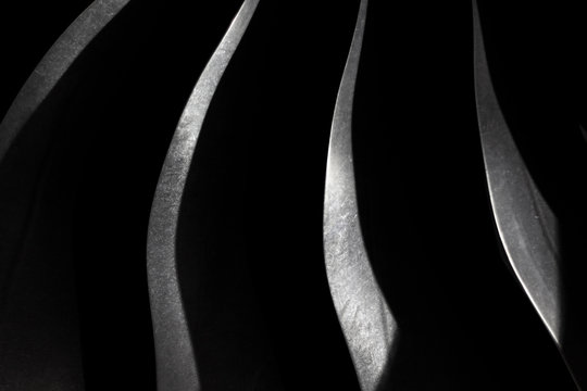 Dark background with silver steel blade, aircraft engine close up, part of a turbojet, modern texture