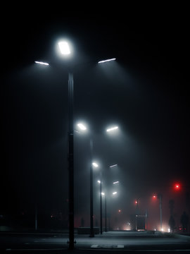 Modern street lights in the fog on empty parking in the night. Cyberpunk style shot. Urban lamp posts against dark sky. Moscow city, Russia.
