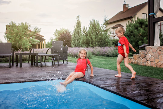 Happy cute sibling, boy and girl, have a fun and splashing each other near the swimming pool