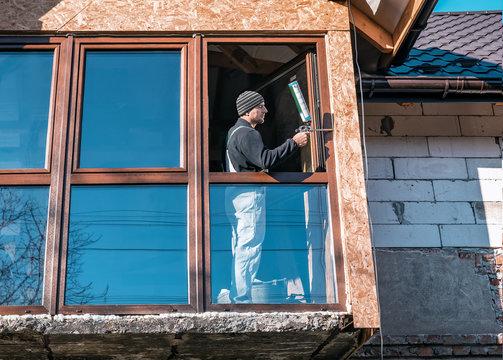 builder works with polyurethane foam at window installation