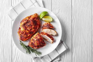 Baked chicken fillets on a white plate, top view