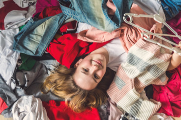 Fast fashion, Girl lies on a bunch of colorful clothes in the dressing room. Concept of recycling, second hand, eco, minimalism, consumption of goods, shopaholic Wall mural