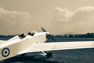 An old light white single engine piston aeroplane taildragger with  roundel engine running and two...