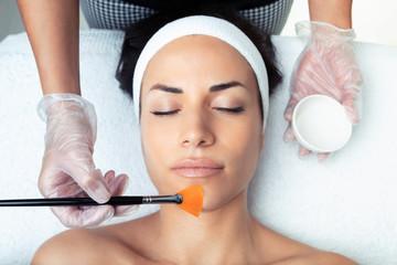 Fototapeta Cosmetologist making a chemistry peeling for rejuvenating the face to woman on the spa center. obraz